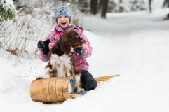Girl and her dog on  a toboggan Royalty Free Stock Images