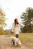 Girl and her dog walking in a park Stock Photography