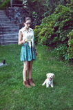 A girl and her dog. A young woman holding a tennis ball with her dog royalty free stock photos