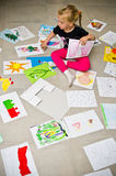 Girl with her drawings on the floor Stock Images