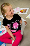 Girl with her drawings on the floor. A preschool girl sitting on the floor presenting her pictures, drawings and paintings done at kindergarten stock image