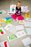 Girl with her drawings on the floor stock image