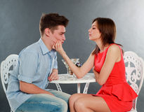 Girl with her drunk and sad boyfriend at table, in studio Royalty Free Stock Photo