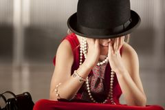 Girl with her face in her hat Stock Images