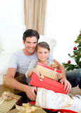 Girl with her father holding a Christmas gift. Happy little girl with her father holding a Christmas gift at home Royalty Free Stock Images