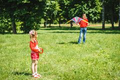 The girl and her father play with a kite. Dad devotes time to the child stock images