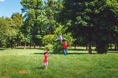 The girl and her father play with a kite. Dad devotes time to the child royalty free stock photo