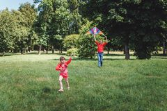 The girl and her father play with a kite. Dad devotes time to the child stock photo