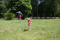 The girl and her father play with a kite. Dad devotes time to the child stock photography