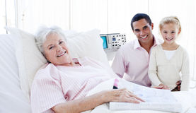 A girl with her father visiting her grandmother Stock Photography