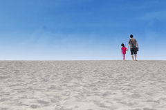 Girl with her father walk on desert Royalty Free Stock Photography
