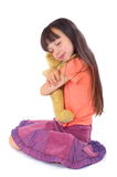 Girl with her favourite toy be. A young girl sits down, closing her eyes and smiling slightly as she hugs her favourite toy close stock image