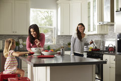 Girl with her female parents, preparing meal in the kitchen Stock Photography