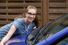 Girl and her first car. Teenage girl embracing her first car royalty free stock photo