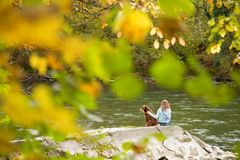 Girl and her friend. A young girl and her best friend sit by the river and relax Royalty Free Stock Photo