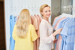 The girl and her friend in the shop clothes royalty free stock images