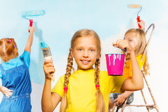 Girl and her friends painting wall. Little girl in yellow holds pail and brush smiling, while her friends paint the wall on a background Royalty Free Stock Photos