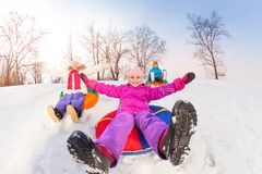 Girl and her friends sliding down hill on tubes Royalty Free Stock Image