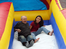 Girl with her grandfather. On the slide Royalty Free Stock Image