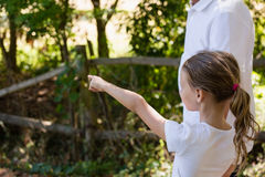 Girl with her grandfather pointing at a distance in the forest Stock Photography