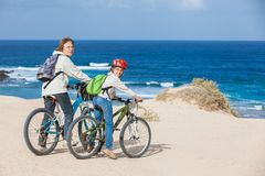 Girl and her grandmother on bikes on the beach. Beautiful girl and her grandmother on bikes on the beach. Lanzarote Royalty Free Stock Image