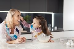 A girl with her grandmother cooks a homemade cake. The girl and her grandmother fool around making home-made pie Royalty Free Stock Photos