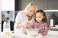 A girl with her grandmother cooks a homemade cake. They mix the dough in a glass bowl Royalty Free Stock Images