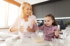 A girl with her grandmother cooks a homemade cake. Girl pours flour into the dough Stock Image