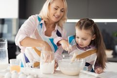 A girl with her grandmother cooks a homemade cake. They knead the dough with their hands Royalty Free Stock Image
