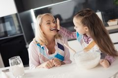 The girl and her grandmother fool around making home-made pie. The girl smeared the woman with a dough and laughs Royalty Free Stock Photography