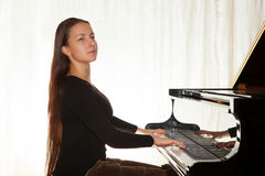 A girl with her hair playing the piano Royalty Free Stock Images