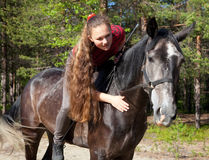 A girl with her hair stroking horse Royalty Free Stock Images
