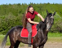 A girl with her hair stroking horse Stock Image