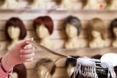 Girl in her hand chooses a hair color wig of a natural blond. A palette of hues of hair color in a store of wigs on a. Blurry background of shelves with maniena stock image