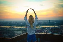 The girl with her hands above her head looks at the sunset from stock photography