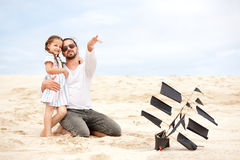 Girl with her happy father flying kite coast ocean Stock Photo