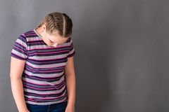 A girl with her head lowered, ashamed of her bad school success stock images