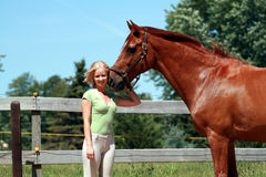 Girl with her horse. In the paddock stock photography