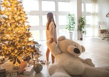 Girl in her house on Christmas with a big bear and a beautiful d royalty free stock photos