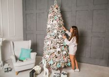 Girl in her house on Christmas with a big gift and a beautiful d. Ecorated Christmas tree; rear view. Christmas celebration concept Royalty Free Stock Images