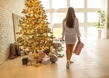 Girl in her house on Christmas with a big gift and a beautiful d stock photography