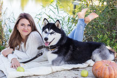 Girl and her husky dog is lying near green river Royalty Free Stock Photo