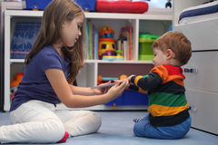 Girl and her little brother arguing with a digital tablet comput Royalty Free Stock Image