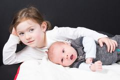 Girl with her little brother lying Playing children on floor on black stock images