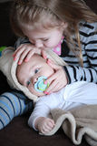 The girl and her little brother with pacifier at home on sofa Stock Image