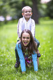 Girl with her little brother playing in the green grass. Stock Images