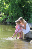 Girl and her little daughter squirting water at the lake Royalty Free Stock Photo
