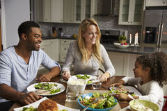 Girl and her mixed race parents dining in their kitchen Stock Images