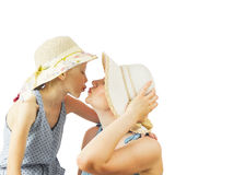 Girl and her mom in hats kissing isolated on white background. Stock Photo