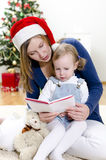 Girl and her mom reading book Stock Image